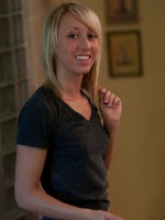 Kelly is making herself up in front of a mirror